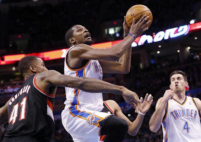 Oklahoma City Thunder forward Kevin Durant, center, shoots in front of Portland Trail Blazers forward Thomas Robinson (41) and teammate Nick Collison (4) in the third quarter of an NBA basketball game in Oklahoma City, Tuesday, Jan. 21, 2014. Oklahoma City won 105-97. (AP Photo/Sue Ogrocki)