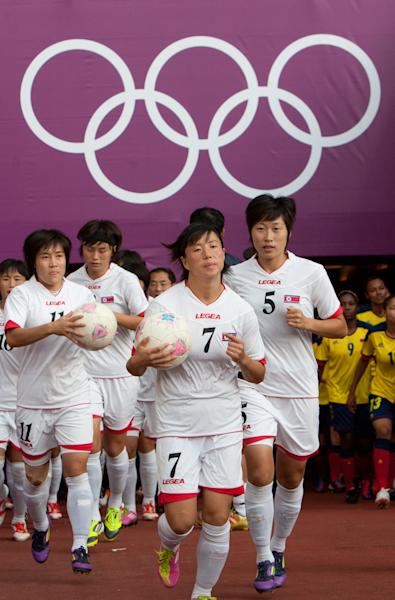 CORRECTS GROUP MATCH TO G INSTEAD OF B- The North Korean women's soccer team runs out on to the field before the group G match between Colombia and North Korea, prior to the start of the London 2012 Summer Olympics, Wednesday, July 25, 2012, at Hampden Park Stadium in Glasgow. (AP Photo/Chris Clark)