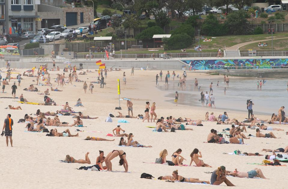Beachgoers are seen on the sand prior to the closure of Bondi Beach in Sydney. Source: AAP