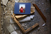 A picture and broken frame lay in the debris in an apartment after it was hit by a rocket fired from the Gaza Strip over night, in Petah Tikva, central Israel, Thursday, May 13, 2021. (AP Photo/Oded Balilty)