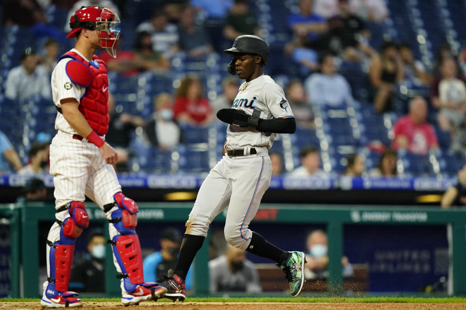 Miami Marlins' Jazz Chisholm Jr., right, scores past Philadelphia Phillies catcher Andrew Knapp on an RBI-sacrifice fly by Adam Duvall during the fourth inning of baseball game, Tuesday, May 18, 2021, in Philadelphia. (AP Photo/Matt Slocum)