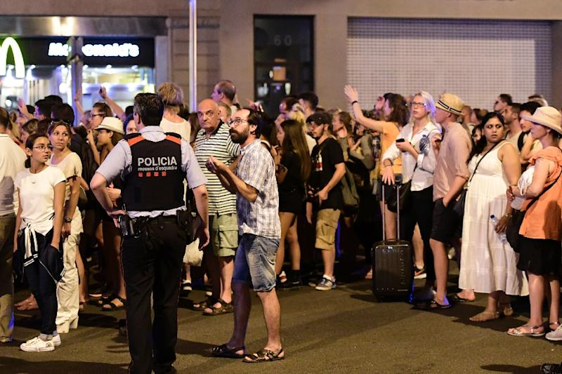 Tourists wait for the police to allow them to come back to their hotel on Las Ramblas boulevard after a van ploughed into the crowd, killing at least 13 people and injuring around 100 others on the Rambla in Barcelona, on August 18, 2017