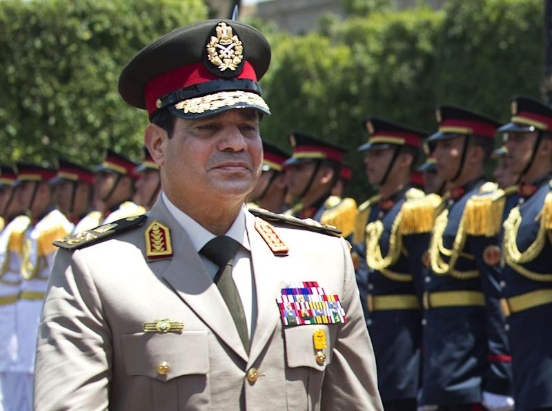 """FILE - In this Wednesday, April 24, 2013 file photo, Egyptian Defense Minister Gen. Abdel-Fattah el-Sissi reviews honor guards during an arrival ceremony for his U.S. counterpart at the Ministry of Defense in Cairo. In dark sunglasses and a uniform studded with medals, Egypt's top general is everywhere, looking down from posters and banners proclaiming him """"lion of the nation."""" Adoring songs vow """"We are behind you."""" Barely a month after he removed the elected president, Gen. Abdel-Fattah el-Sissi is riding a wave of adulation _ in part, state fueled _ that is drawing comparisons between him and modern Egypt's first charismatic strongman, Gamal Abdel-Nasser. Some are warning that the personality cult could pave the way to new authoritarianism. (AP Photo/Jim Watson, Pool, File)"""