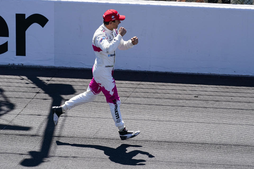 Helio Castroneves, of Brazil, runs down the track as he celebrates after winning the Indianapolis 500 auto race at Indianapolis Motor Speedway in Indianapolis, Sunday, May 30, 2021. (AP Photo/Darron Cummings)
