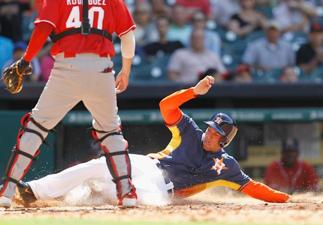 Houston's George Springer slides safely at home in the seventh inning in front of Rojos del Aguila de Veracruz's catcher Leonardo Rodriguez during a spring exhibition baseball game on Sunday, March 30, 2014, in Houston. Houston won 6-1. (AP Photo/Bob Levey)