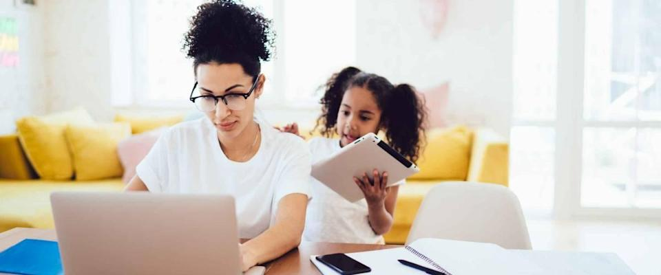 Little girl standing in bright room and showing tablet to mother while parent in glasses working in front of laptop.