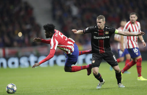 Atletico Madrid's Thomas Partey, left, fights for the ball against Leverkusen's Lars Bender during the Champions League Group D soccer match between Atletico Madrid and Bayer Leverkusen at Wanda Metropolitano stadium in Madrid, Spain, Tuesday, Oct. 22, 2019. (AP Photo/Bernat Armangue)