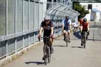 Bicyclists ride across a pedestrian bridge in the morning to escape from the heat during a record setting heat wave in Portland, Ore., Sunday, June 27, 2021. Yesterday set a record high for the day with more records expected today. (AP Photo/Craig Mitchelldyer)