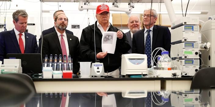 U.S. President Donald Trump displays a photo of the coronavirus beside Georgia Governor Brian Kemp, HHS Secretary Alex Azar, and CDC Associate Director for Laboratory Science and Safety Steve Monroe during a tour of the Center for Disease Control on March 6, 2020.