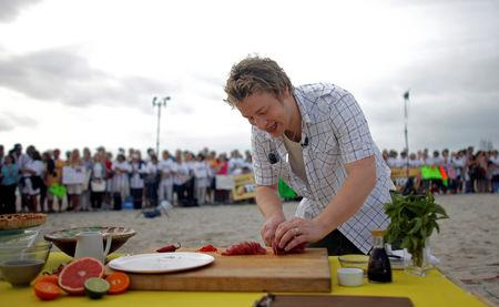 """FILE PHOTO: The Naked Chef Jamie Oliver slices fish during an appearance on NBC's """"Today"""" show in Miami Beach, Florida February 22, 2008. REUTERS/Eric Thayer/File Photo"""