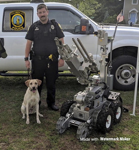 """In this undated photo released by the Columbia, S.C. Police Department, Master Police Officer David Hurt is seen with his police dog """"Turbo."""" Hurt was suspended without pay for five days after Turbo died from excessive heat in July 2018 when the dog was left in a police vehicle for more than six hours. (Columbia, S.C. Police Department via AP)"""