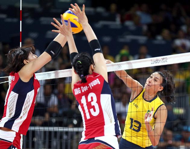 LONDON, ENGLAND - AUGUST 01:  Sheilla Castro #13 of Brazil spikes the ball as Dae-Young Jung #13 of Korea defends during Women's Volleyball on Day 5 of the London 2012 Olympic Games at Earls Court on August 1, 2012 in London, England.  (Photo by Elsa/Getty Images)