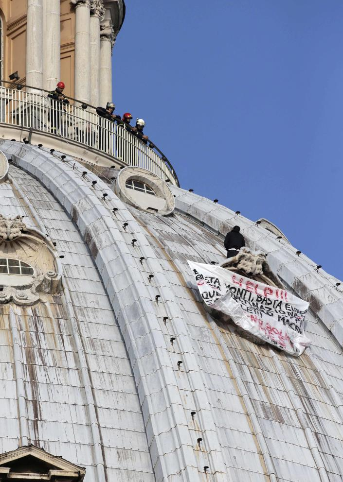 """Firefighters look at Italian businessman Marcello di Finizio standing by his banner with writing reading in Italian """"Help!! Enough Monti (Italian Premier Mario Monti), enough Europe, enough multinationals, you are killing all of us. Development?? This is a social butchery!!"""" as he protests on St. Peter's 130-meter-high (42-feet-high) dome, at the Vatican, Wednesday, Oct. 3, 2012. Di Finizio eluded Vatican security Tuesday and scaled the dome of St. Peter's Basilica to protest against the Italian government and European Union policies. Officials said Wednesday that the man, who identified himself as the owner of a beach resort, refused appeals from government ministers offering to meet with him if he would come down. (AP Photo/Andrew Medichini)"""