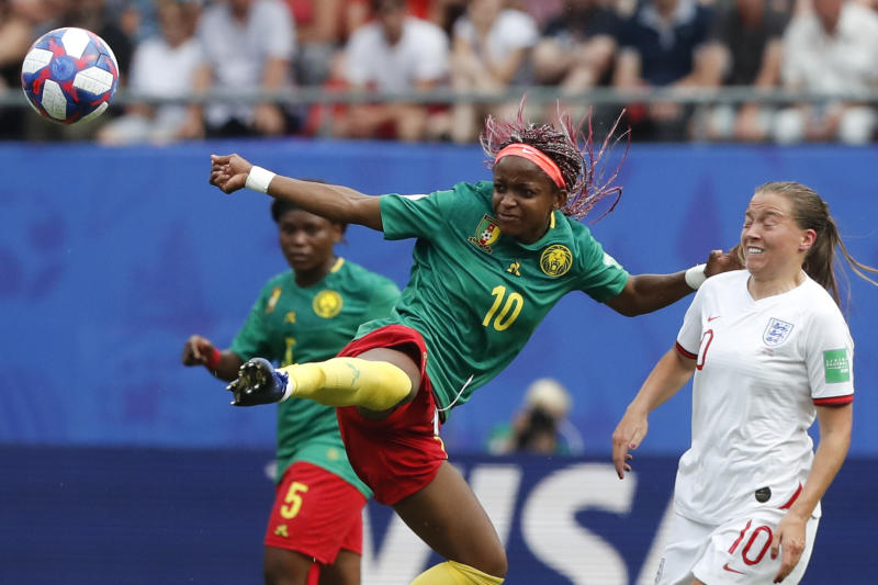 Cameroon's Jeannette Yango, left, reaches for the ball as in action with England's Fran Kirby during the Women's World Cup round of 16 soccer match between England and Cameroon at the Stade du Hainaut stadium in Valenciennes, France, Sunday, June 23, 2019. (AP Photo/Michel Spingler)