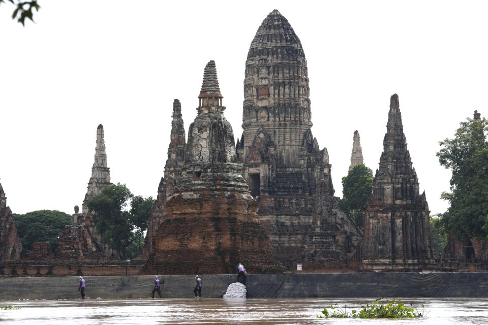 Soldiers stack sandbags to protect Wat Chaiwatthanaram from possible rising flood waters in Ayutthaya province, north of Bangkok, Thailand, Monday, Sept. 27, 2021. Seasonal monsoon rains may worsen flooding that has already badly affected about a third of Thailand, officials said Monday as flood gates and pumping stations were being used to mitigate the potential damage. (AP Photo/Sakchai Lalit)