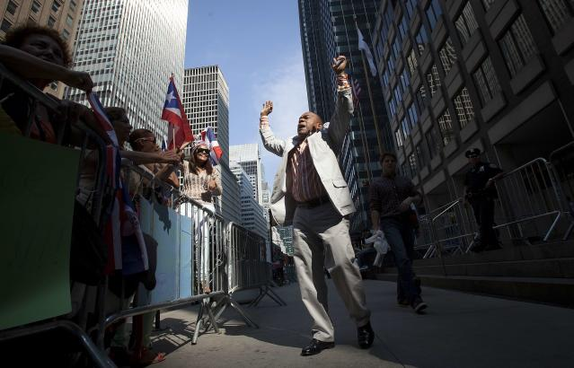 A supporter of baseball player Alex Rodriguez chants in a demonstration outside Major League Baseball's headquarters in New York October 4, 2013. New York Yankees player Rodriguez has sued Major League Baseball and its Commissioner, accusing them of improperly gathering evidence to destroy his reputation and career. Rodriguez, suspended from 211 games by Major League Baseball for doping, claims MLB interfered with his contracts and business relationships. REUTERS/Carlo Allegri (UNITED STATES - Tags: SPORT BASEBALL LAW)