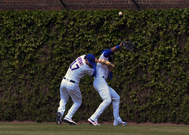 Chicago Cubs center fielder Jason Heyward, right, and right fielder Kris Bryant (17) collide while chasing a ball hit by Cincinnati Reds'c Eugenio Suarez (7) during the sixth inning of a baseball game Sunday, May 26, 2019, in Chicago. Bryant was charged with an error on the play. (AP Photo/Matt Marton)