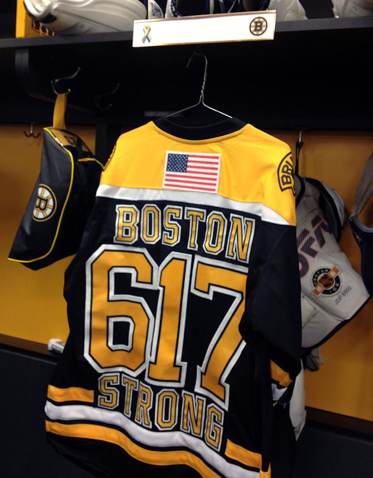 """A Boston Bruins jersey with the number of Boston's area code and the words """"Boston Strong"""" hangs in the locker of Bruins player Jay Pandolfo at TD Garden in Boston, Wednesday, April 17, 2013, after an NHL hockey game against the Buffalo Sabres in the aftermath of Monday's Boston Marathon bombings. (AP Photo/Jimmy Golen)"""