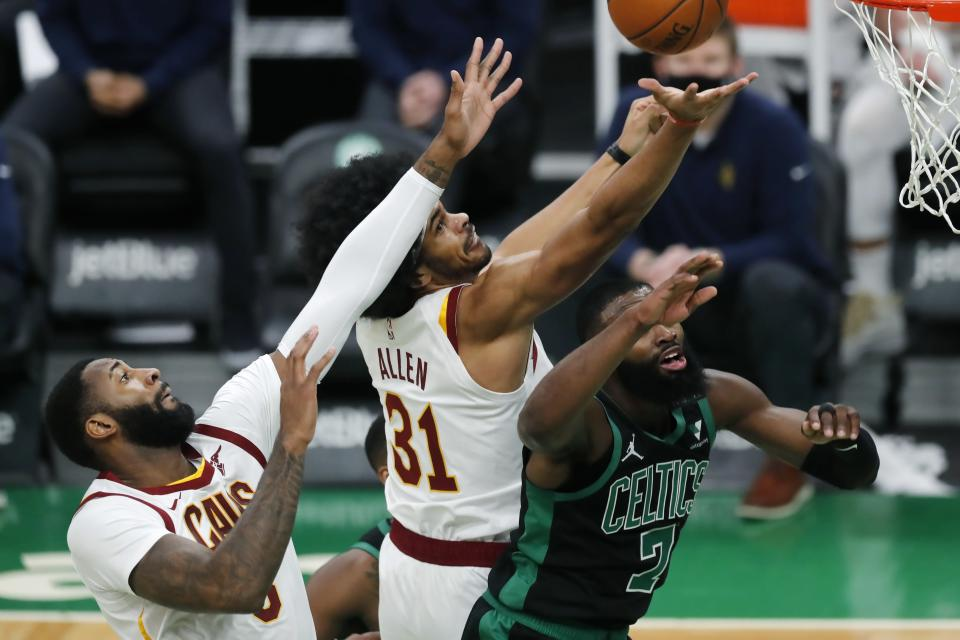Cleveland Cavaliers' Andre Drummond, left, and Jarrett Allen, center, battle Boston Celtics' Jaylen Brown, right, for a rebound during the first half of an NBA basketball game, Sunday, Jan. 24, 2021, in Boston. (AP Photo/Michael Dwyer)
