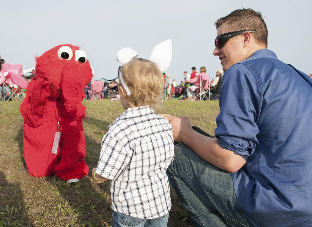 A volunteer dressed up as the character Elmo kneels in the manner of New York Jets quarterback Tim Tebow, before Tebow's speech during Celebration Church's Easter service in Georgetown, Texas, Sunday, April 8, 2012. (AP Photo/William Philpott)