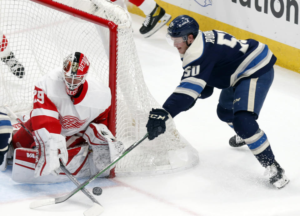 Detroit Red Wings goalie Thomas Greiss, left, stops a shot by Columbus Blue Jackets forward Eric Robinson during the first period of an NHL hockey game in Columbus, Ohio, Friday, May 7, 2021. (AP Photo/Paul Vernon)