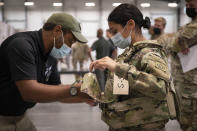"""In this image provided by the U.S. Army, Sgt. Katiushka Rivera, a soldier assigned to the 82nd Airborne gets fitted for a modular scalable vest (MSV) during a fielding event in Fort Bragg, N.C., on Sept. 13, 2021. The Army for the first time, began handing out armor that now comes in three additional sizes, and can be adjusted in multiple ways to fit better and allow soldiers to move faster and more freely. The so-called """"modular, scalable vest"""" was is being distributed to soldiers at Fort Bragg, N.C., along with new versions of the combat shirt that are tailored to better fit women, with shorter sleeves and a flare at the bottom where it hits their hips. (Jason Amadi/U.S. Army via AP)"""