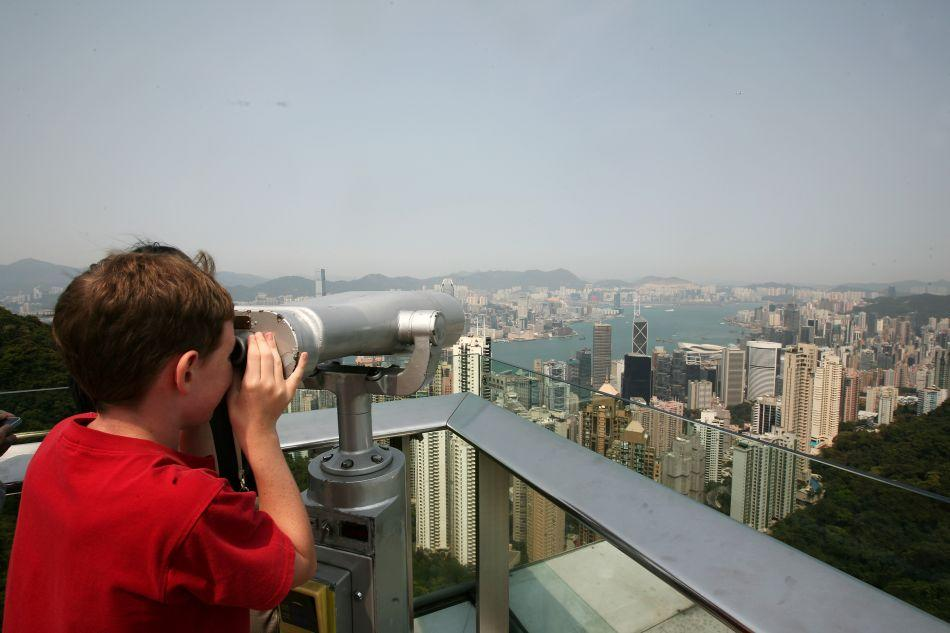 A young boy looks through binoculars at the view from the Sky Terrace 428.