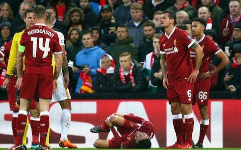Alex Oxlade-Chamberlain grimaces on the ground after getting injured during the Champions League semifinal, first leg - Credit: Dave Thompson/AP