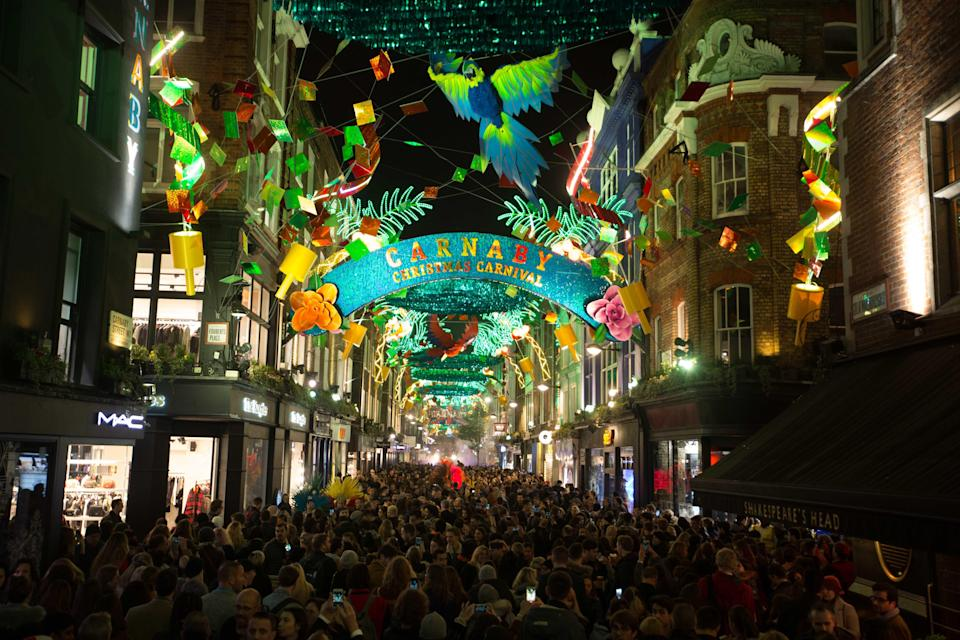 <p>Crowds gather for the Carnaby Christmas lights switch-on in Carnaby, London, which features a carnival theme. (PA) </p>