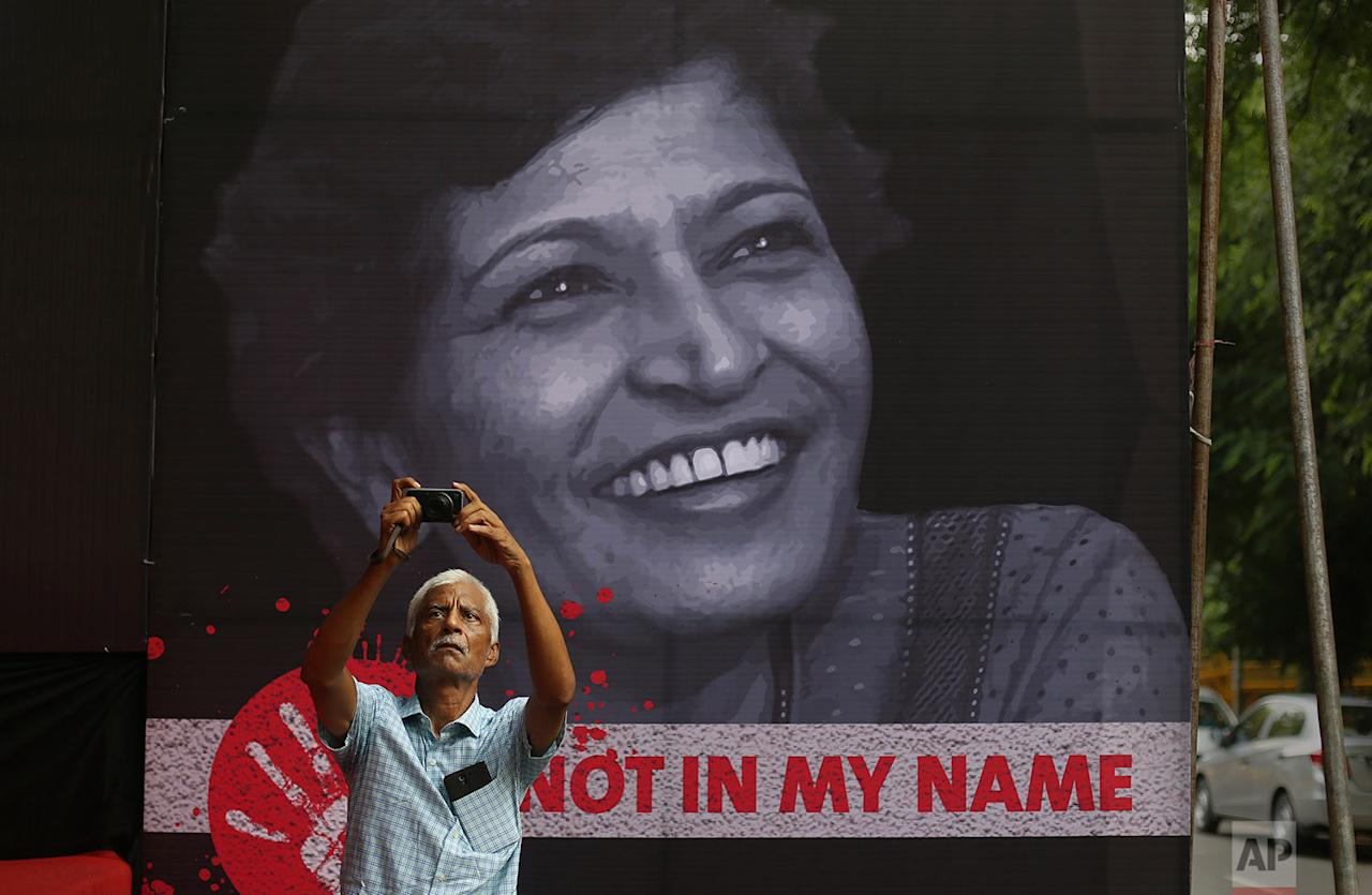 <p>An Indian man takes a photographs during a protest condemning the killing of journalist Gauri Lankesh, protrait in background, in New Delhi, India. Lankesh's killing has provoked outrage and anguish across the country, with thousands protesting what they see as an effort to silence critics of India's ruling Hindu nationalist party. (AP Photo/Altaf Qadri) </p>