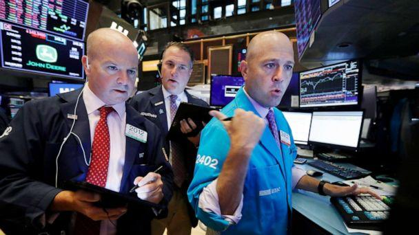 PHOTO: Traders Patrick Casey, left, and Jonathan Corpina, center, work with specialist Jay Woods on the floor of the New York Stock Exchange, Aug. 14, 2019. (Richard Drew/AP)