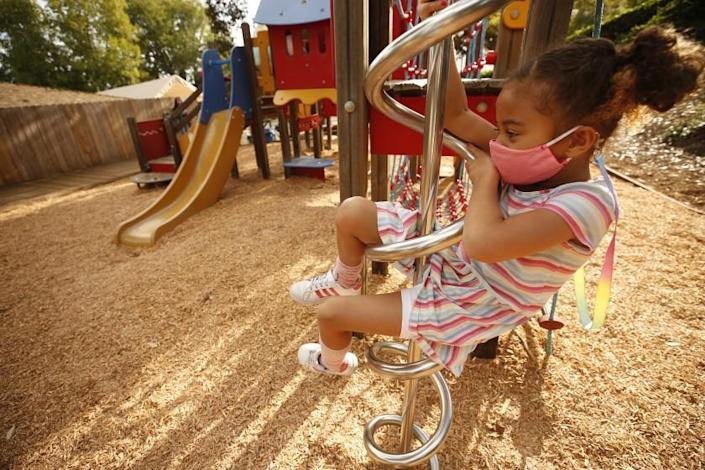 PALOS VERDES, CA - NOVEMBER 05: Kindergarten student Scarlett Bates on the playground equipment as students try to practice social distancing at Chadwick School in Palos Verdes as students find themselves in smaller class sizes staggered on various days of the week while practicing social distancing and wearing masks. Chadwick is open for kindergarten to second grade with later grades coming back to campus soon. Chadwick School started in 1935. There is wide latitude in terms of how schools can bring kids back to campus In LA County. One option is waivers, while the other is a stipulation that allows schools to bring back 25% of their populations if the students are high needs. Smaller school districts and private schools in more affluent areas are taking advantage of it in greater ways than school districts, raising another set of equity concerns around what children are getting in-person education sooner. Chadwick School on Thursday, Nov. 5, 2020 in Palos Verdes, CA. (Al Seib / Los Angeles Times