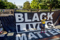 FILE - In this June 8, 2020, file photo, the White House is visible behind a woman who holds her fist up as she poses for a photograph with a large banner that reads Black Lives Matter hanging on a security fence in Washington, after days of protests over the death of George Floyd. (AP Photo/Andrew Harnik, File)
