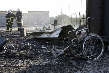 French firemen stand near debris the day after a fire destroyed large swathes of the Grande-Synthe migrant camp near Dunkirk in northern France April 11, 2017 following skirmishes on Monday that injured several people.  REUTERS/Pascal Rossignol