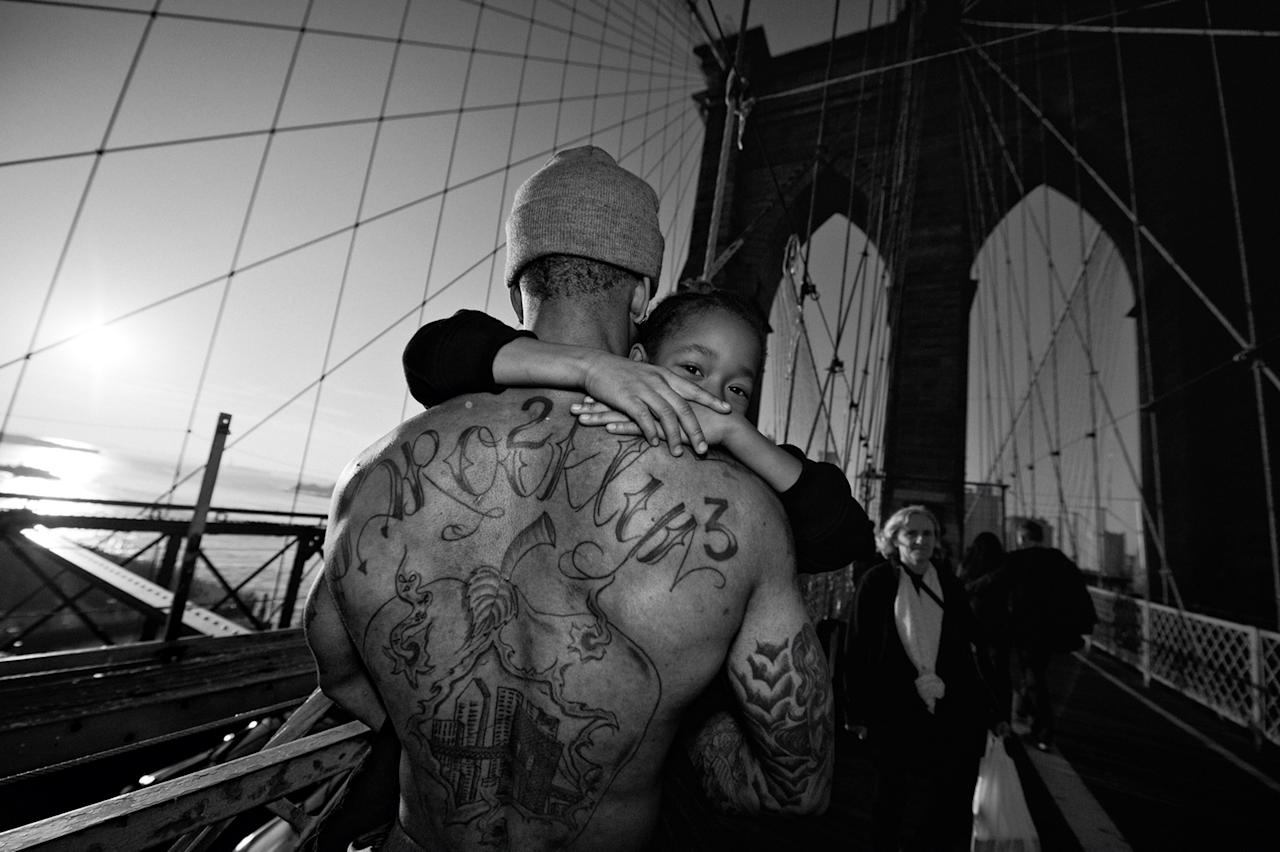 <p>Jerell Willis carries his son Fidel across the Brooklyn Bridge, Brooklyn, N.Y., 2012. (Photograph © Zun Lee) </p>