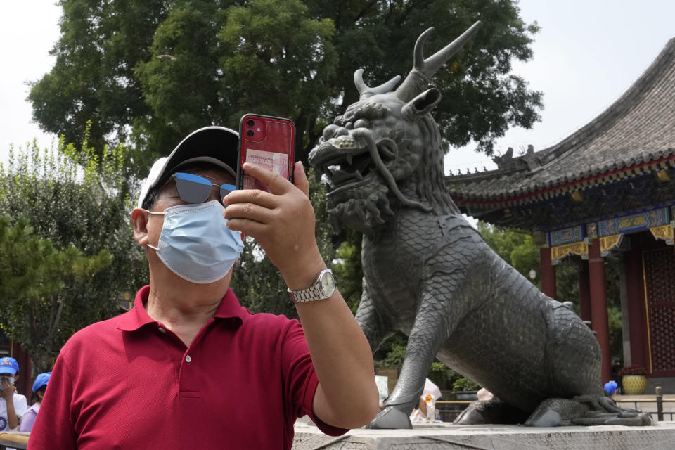 A tourist takes a photo near a statue of a mystical beast at the Summer Palace in Beijing Tuesday, Aug. 3, 2021. The current coronavirus outbreaks in China, while still in the hundreds of cases in total, have spread much more widely than previous ones, reaching multiple provinces and cities including the capital, Beijing. Many of the cases have been identified as the highly contagious delta variant that is driving a resurgence in many countries. (AP Photo/Ng Han Guan)