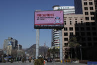 """A huge screen displays precautions against the COVID-19 is seen in downtown Seoul, South Korea, Sunday, Feb. 23, 2020. South Korea and China both reported a rise in new virus cases on Sunday, as the South Korean prime minister warned that the fast-spreading outbreak linked to a local church and a hospital in the country's southeast had entered a """"more grave stage."""" (AP Photo/Lee Jin-man)"""
