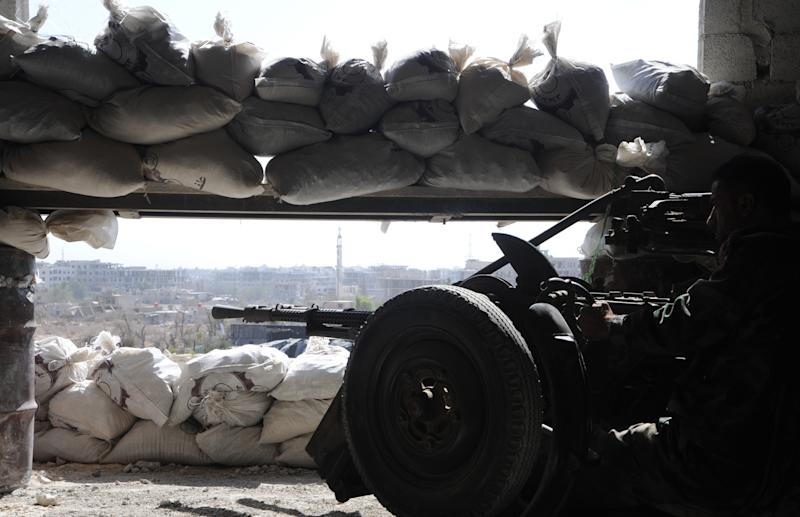 A Syrian soldier guards a post with a heavy machine gun in Jobar, in rural Damascus, on October 18, 2014 (AFP Photo/)