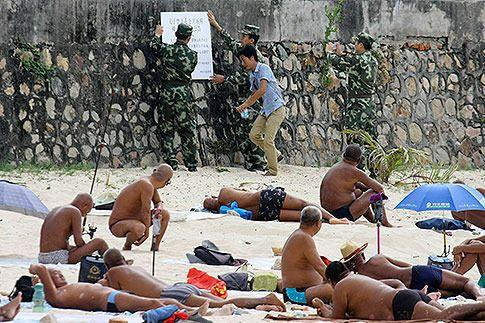 Sunbathers watch as government officials put up a notice on banning nudity in public areas, at a beach in Sanya, Hainan province on February 8, 2014. Photo: Reuters