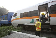 A worker checks on the derailed train near Taroko Gorge in Hualien, Taiwan on Saturday, April 3, 2021. The train partially derailed in eastern Taiwan on Friday after colliding with an unmanned vehicle that had rolled down a hill, killing and injuring dozens. (AP Photo/Chiang Ying-ying)