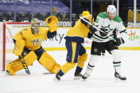 Nashville Predators goaltender Juuse Saros (74) reaches for a shot as Predators defenseman Ryan Ellis (4) and Dallas Stars center Joe Pavelski (16) duck out of the way in the first period of an NHL hockey game Sunday, April 11, 2021, in Nashville, Tenn. (AP Photo/Mark Humphrey)