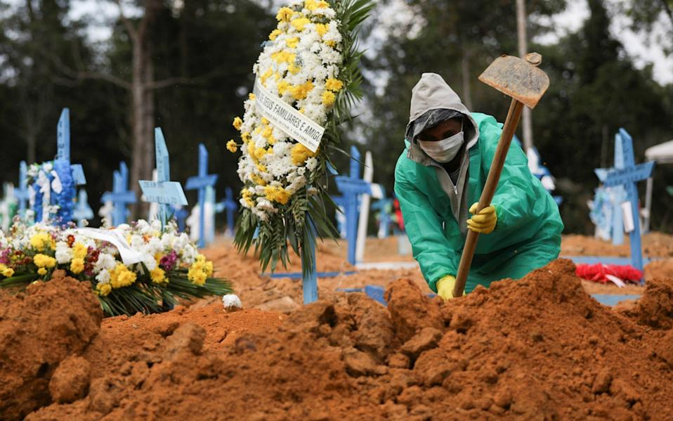 A gravedigger works during a funeral at the Parque Taruma cemetery in Manaus, Brazil - BRUNO KELLY / Reuters