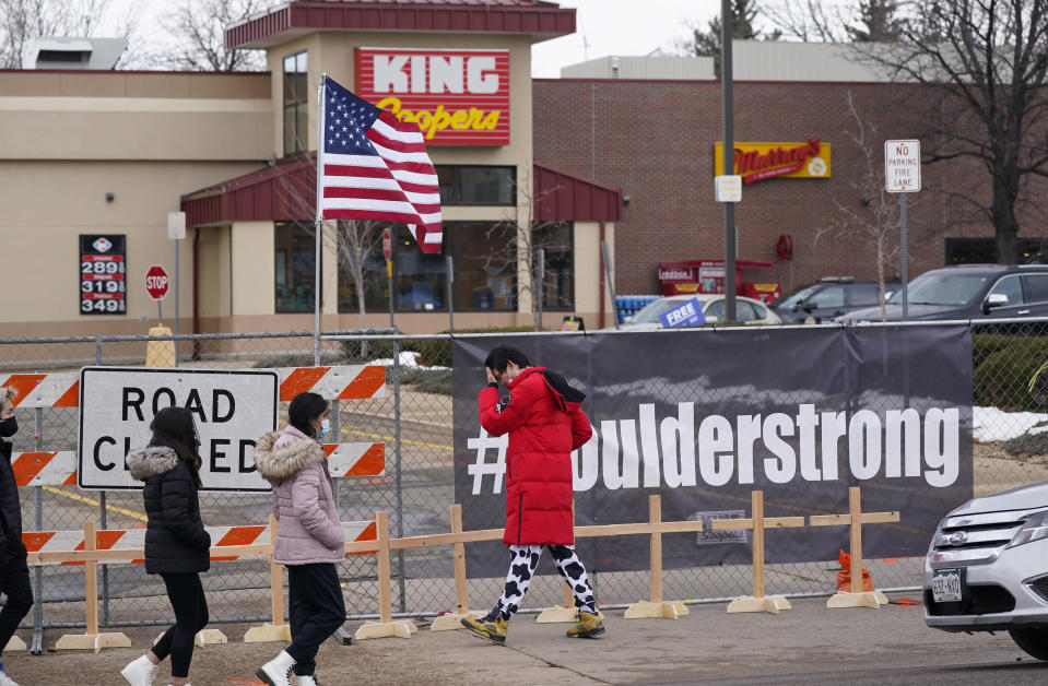 Mourners walk along a fence put up around the parking lot Tuesday, March 23, 2021, where a mass shooting took place in a King Soopers grocery store, in Boulder, Colo. (AP Photo/David Zalubowski)