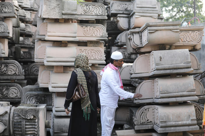 Indian Muslims look at pillars lying at a workshop for the construction of a Rama temple ahead of its groundbreaking ceremony in Ayodhya, in the Indian state of Uttar Pradesh, Monday, Aug. 3, 2020. As Hindus prepare to celebrate the groundbreaking of a long-awaited temple at a disputed ground in northern India, Muslims say they have no firm plans yet to build a new mosque at an alternative site they were granted to replace the one torn down by Hindu hard-liners decades ago. (AP Photo/Rajesh Kumar Singh)