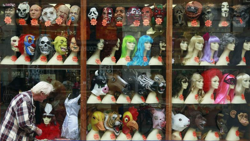 A man looks at the window of a novelty shop displaying joke masks and wigs ahead of the Halloween season in central Dublin