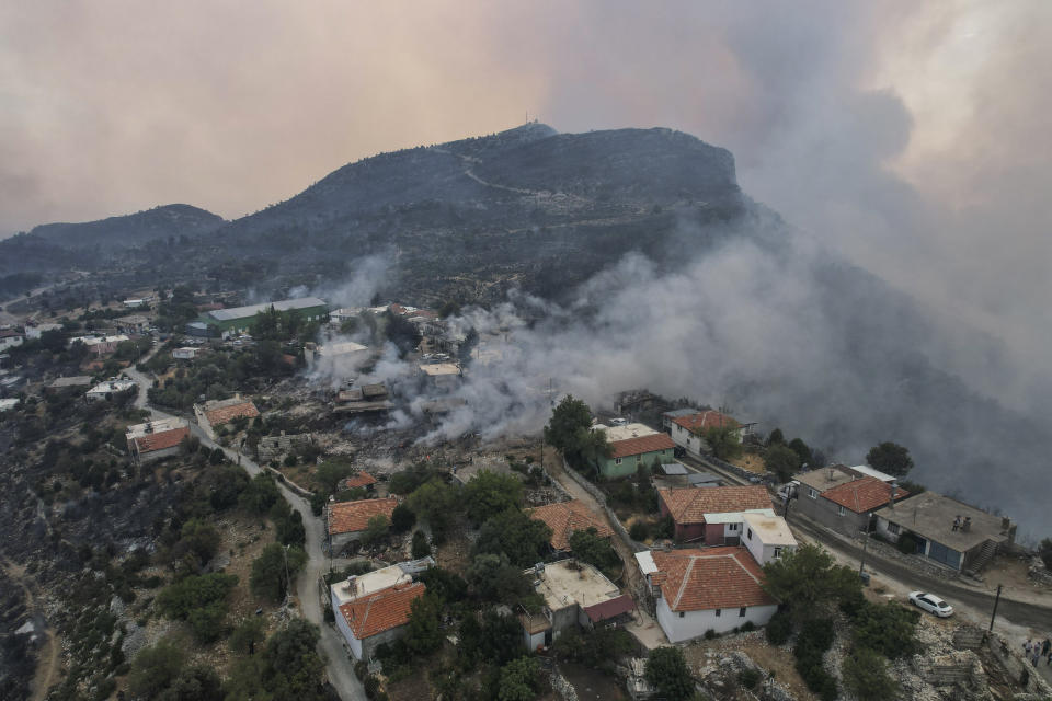 An aerial view of the burning Sirtkoy village, near Manavgat, Antalya, Turkey, Sunday, Aug. 1, 2021. More than 100 wildfires have been brought under control in Turkey, according to officials. The forestry minister tweeted that five fires are continuing in the tourist destinations of Antalya and Mugla. (AP Photo)