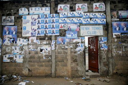 Election posters are seen pasted on a wall at the entrance to Benin Tennis Club, a day before the presidential election in Cotonou, March 5, 2016. REUTERS/Akintunde Akinleye