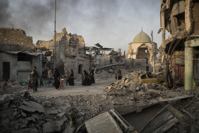 Fleeing Iraqi civilians walk past the heavily damaged al-Nuri mosque during fights between Iraqi security forces and Islamic State militants in the Old City of Mosul, Iraq. (Photo: Felipe Dana/AP)