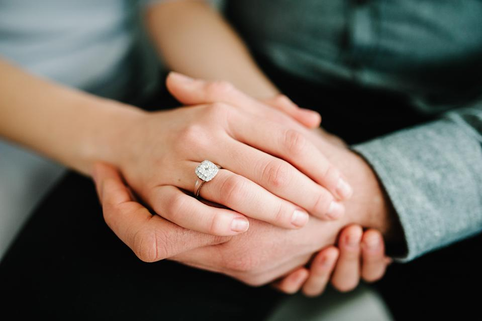 Close up of an elegant engagement diamond ring on woman finger. love and wedding concept.