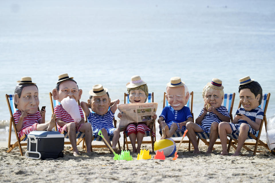 Climate activists from Oxfam, wearing giant heads depicting the leaders of the G7, sit on beach chairs as they participate in an action on Swanpool Beach in Falmouth, Cornwall, England, Saturday, June 12, 2021. Leaders of the G7 gather for a second day of meetings on Saturday, in which they will discuss COVID-19, climate, foreign policy and the economy. Leaders from left, Italy's Prime Minister Mario Draghi, Japan's Prime Minister Yoshihide Suga, French President Emmanuel Macron, German Chancellor Angela Merkel, U.S. President Joe Biden, British Prime Minister Boris Johnson and Canadian Prime Minister Justin Trudeau. (AP Photo/Alastair Grant)